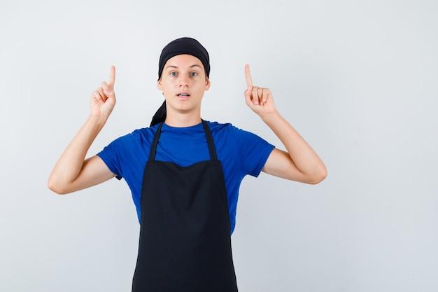 Mannelijke tienerkok wijst omhoog in t-shirt, schort en ziet er zelfverzekerd uit. vooraanzicht.