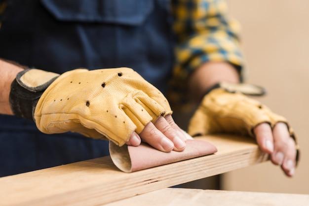 Mannelijke timmerman die de houten plank met schuurpapier gladmaakt