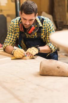 Mannelijke timmerman die het houten blok met heerser en potlood meet