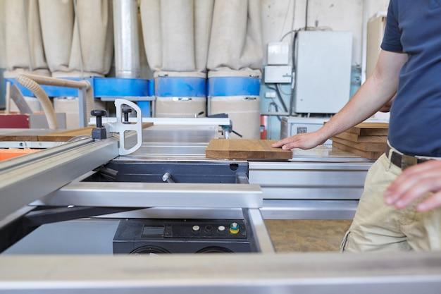 Mannelijke timmerman die houten designmeubelen maakt voor een individuele particuliere bestelling