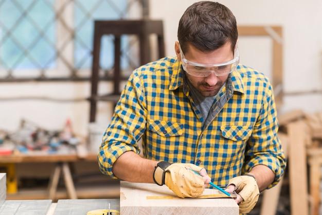 Mannelijke timmerman die meting met heerser op houten blok neemt