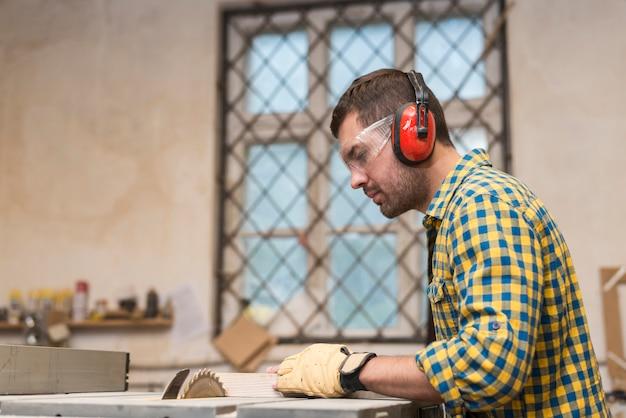 Mannelijke timmerman die veiligheidsbril en oorverdediger draagt die het blok op cirkelzaagblad snijdt