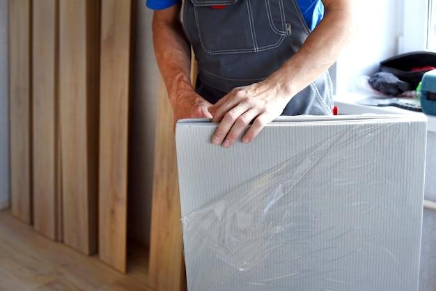 Mannelijke timmerman kiest een laminaatsubstraat. het concept van werkende beroepen.