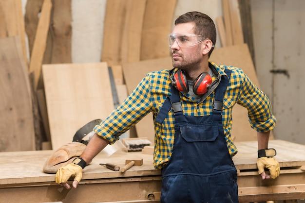 Mannelijke timmerman met veiligheidsbril en oorverdediger rond zijn hals die zich voor houten werkbank bevinden