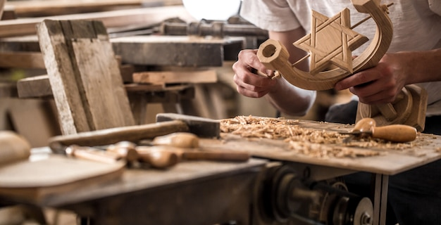 Mannelijke timmerman werken met een houtproduct, handgereedschap