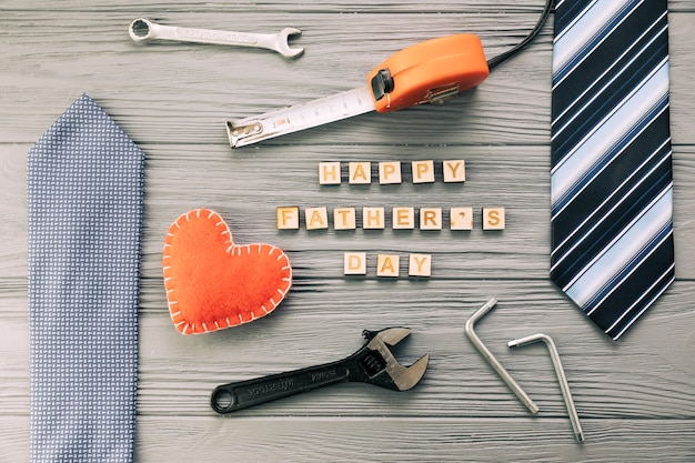 Mannelijke toebehoren dichtbij instrumenten en de gelukkige woorden van de vadersdag met hart