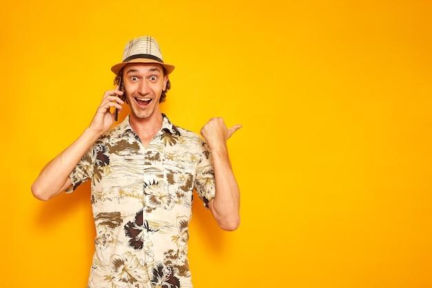 Mannelijke toerist die aan de telefoon praat met zijn vinger wijzend op een leeg gebied, geïsoleerde gele achtergrond