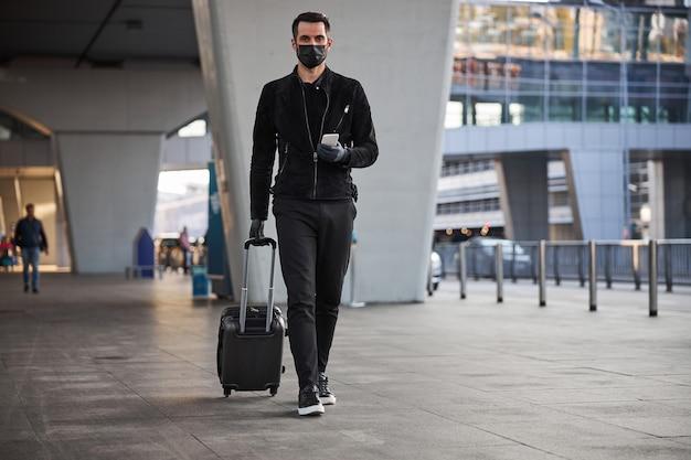Mannelijke toerist die met bagage loopt tijdens de pandemie