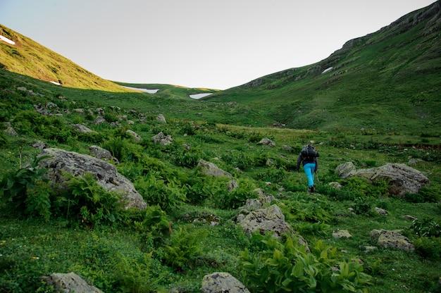 Mannelijke toerist die met rugzak door vallei loopt