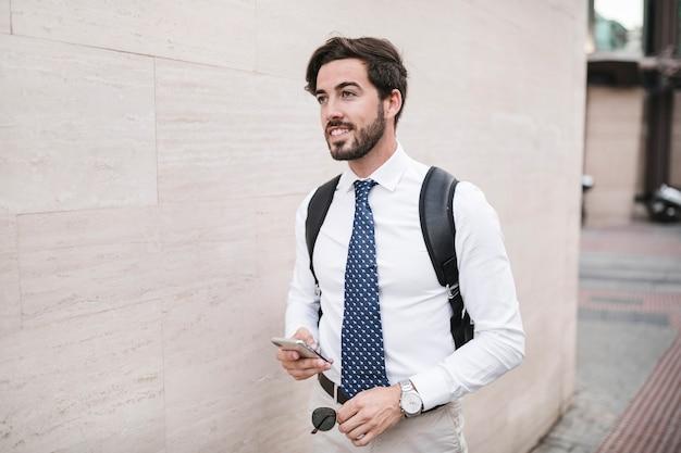 Mannelijke toerist die zich dichtbij muur met zijn cellphone bevindt