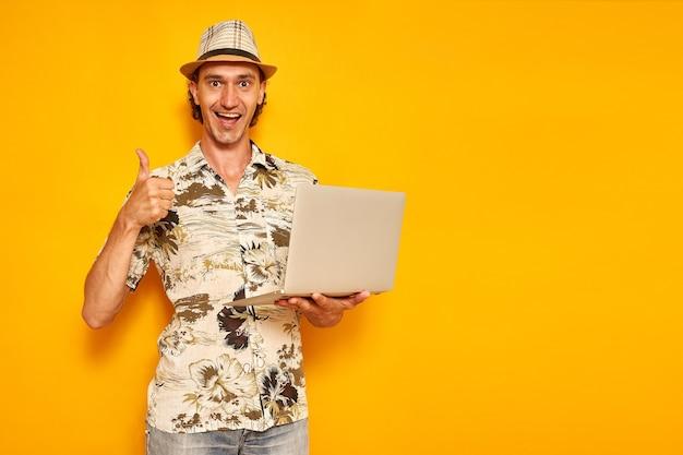 Mannelijke toerist houdt laptop in zijn hand en geeft duimen omhoog geïsoleerde gele achtergrondruimte voor tekst