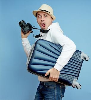 Mannelijke toerist met een koffer in zijn handen, handbagage van een toerist Premium Foto