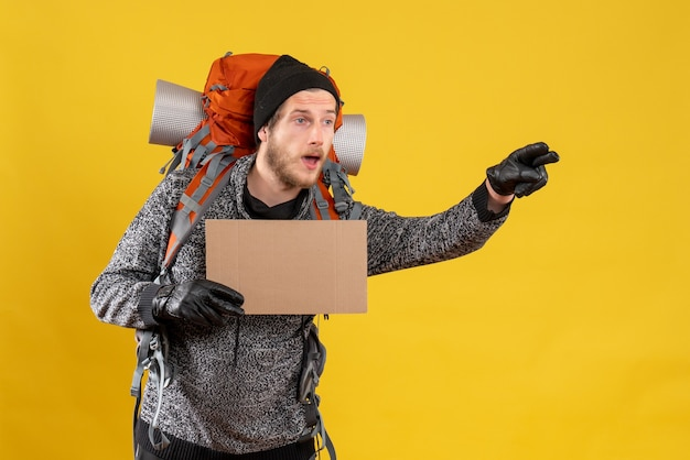 Mannelijke toerist met leren handschoenen en rugzak met blanco kartonnen liften