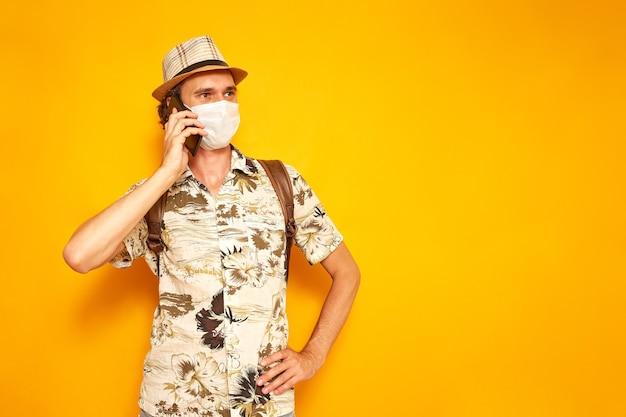 Mannelijke toerist met telefoon in zijn hand praat op smartphone op vakantie geïsoleerde gele achtergrond
