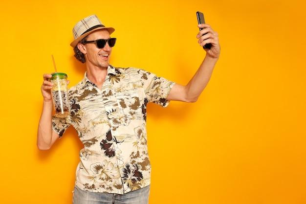 Mannelijke toerist neemt selfie op telefoon met tropisch drankje in de hand geïsoleerde gele achtergrond kopie ruimte