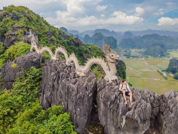 Mannelijke toerist op de achtergrond van een geweldig enorm drakenstandbeeld op de kalkstenen bergtop in de buurt van hang mua