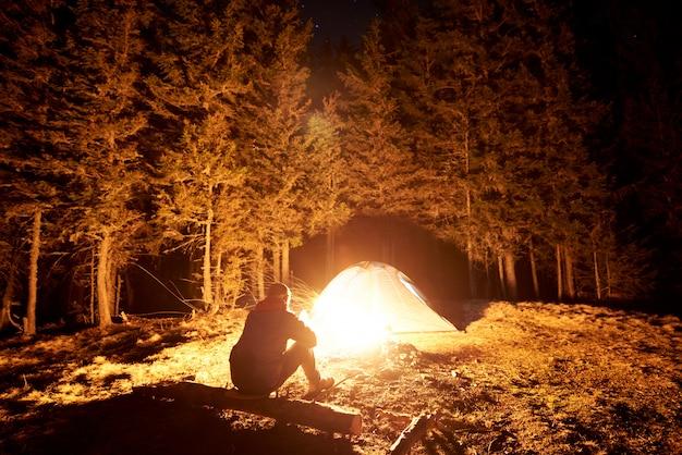 Mannelijke toerist rust 's nachts uit in zijn kamp bij het kampvuur en de tent onder een prachtige nachthemel vol sterren en de maan en geniet van een nachtscène in de bergen