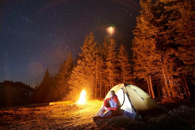 Mannelijke toerist rust 's nachts uit in zijn kamp nabij het bos