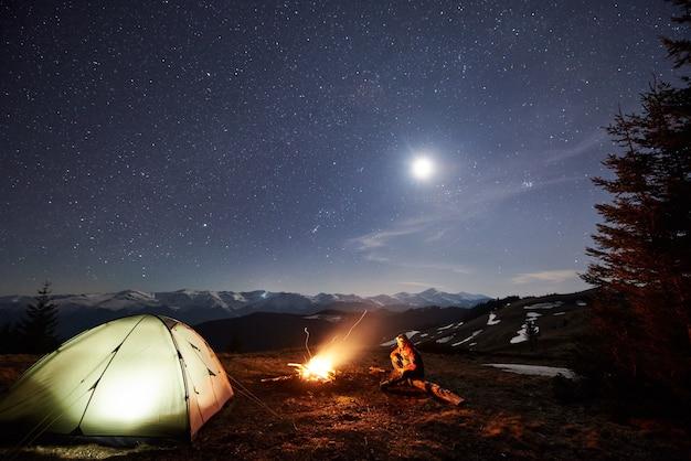 Mannelijke toerist rusten 's nachts in zijn kamp in de buurt van het bos.