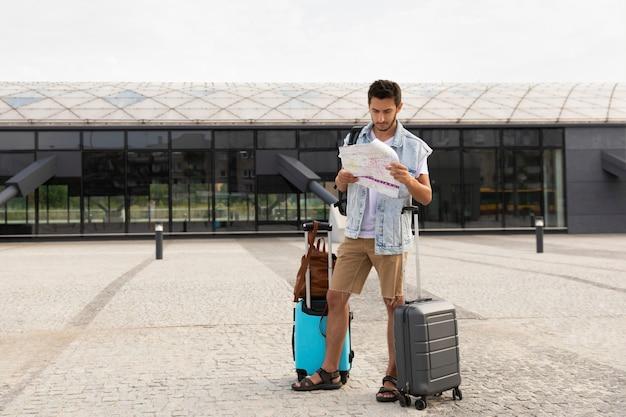 Mannelijke toerist staat bij het busstation en bestudeert een kaart van de stad