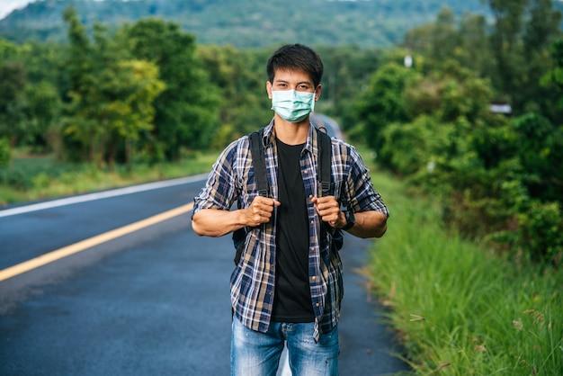 Mannelijke toeristen die een masker dragen, die een rugzak op de weg dragen.