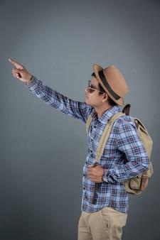 Mannelijke toeristen die grijze achtergrond backpacken.
