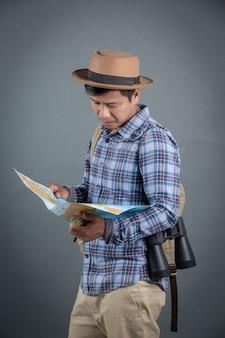 Mannelijke toeristen die rugzakken dragen die een grijze achtergrondkaart dragen.