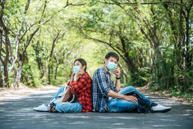 Mannelijke toeristen een vrouw die een masker draagt en op straat zit.
