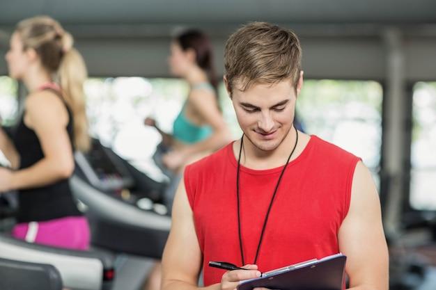 Mannelijke trainer die aan camera in gymnastiek glimlacht