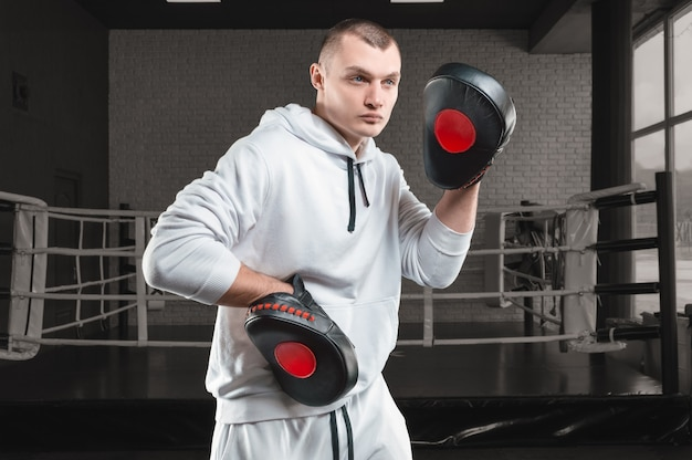 Mannelijke trainer in de sportschool tegen de ring houdt boksen poten. gemengd vechtsportenconcept.