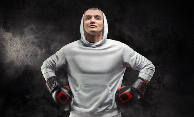 Mannelijke trainer poseren in de studio met bokshandschoenen. witte hoodie. gemengd vechtsportenconcept.