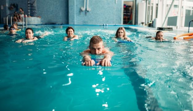 Mannelijke trainer zwemt met vrouwelijke aqua-aerobicsgroep