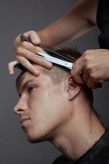 Mannelijke trending kapsel bij kapper met een schaar en haarborstel.