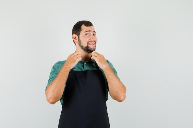 Mannelijke tuinman houdt zijn kraag in t-shirt, schort en ziet er vrolijk uit, vooraanzicht.
