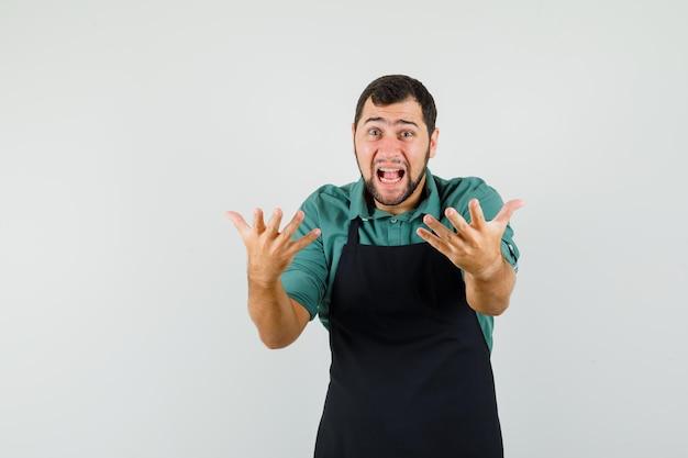 Mannelijke tuinman in t-shirt, schort die handen op een agressieve manier opheft en geagiteerd kijkt, vooraanzicht.