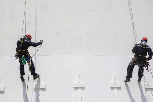 Mannelijke twee werknemer kabeltoegang inspectie van dikte opslag propaan witte tank industrie