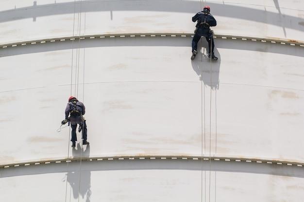 Mannelijke twee werknemer touwtoegang inspectie van dikte opslag witte tank industrie thickness