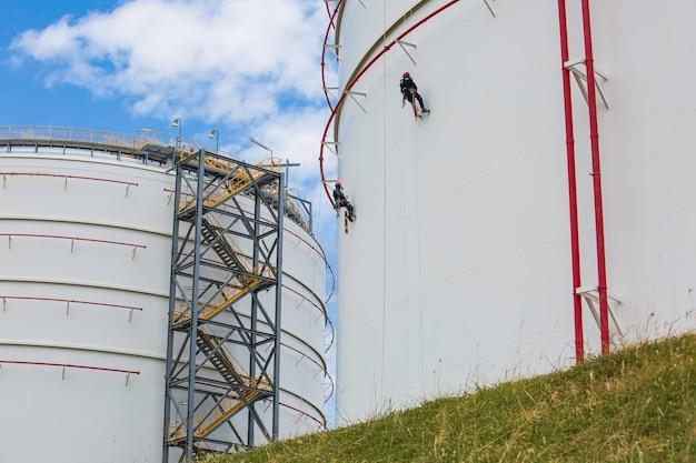 Mannelijke twee werknemers controleren de kabeltoegang van het dak naar de tank van het dak van de dikte van de schaalplaat van de opslagtank voor gasveiligheid op hoogte.