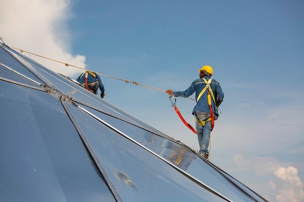 Mannelijke twee werknemers touwtoegangshoogte veiligheid verbinden met acht knopen veiligheidsharnas