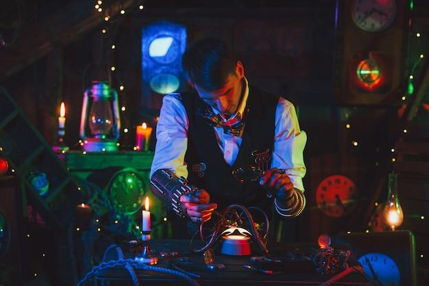 Mannelijke uitvinder in een steampunk-pak repareert het mechanisme. een horlogemaker met gereedschap en een vergrootglas werkt