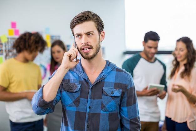 Mannelijke uitvoerend die op mobiele telefoon spreekt