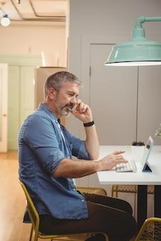 Mannelijke uitvoerend praten op mobiele telefoon tijdens het gebruik van digitale tablet
