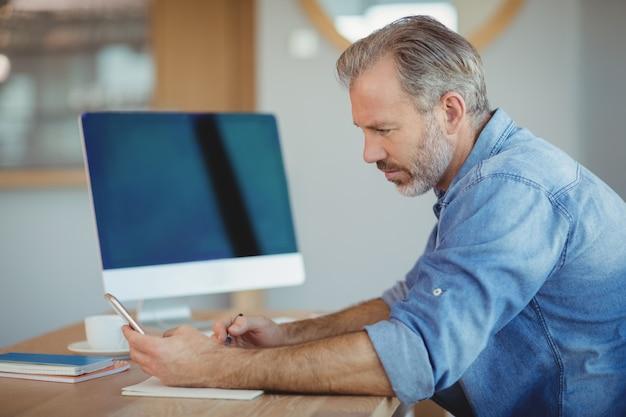 Mannelijke uitvoerend schrijven in de organisator tijdens het gebruik van de mobiele telefoon