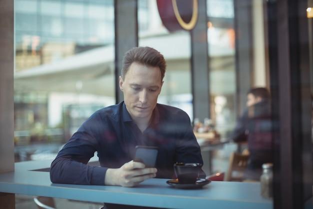 Mannelijke uitvoerende macht met behulp van mobiele telefoon aan balie