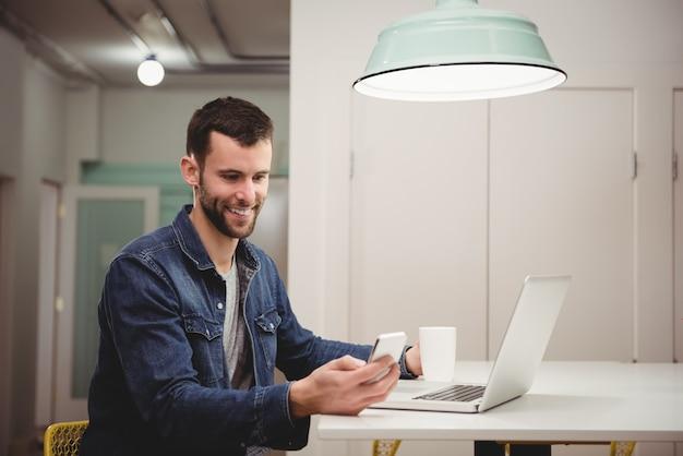 Mannelijke uitvoerende macht met behulp van mobiele telefoon terwijl het hebben van koffie op kantoor