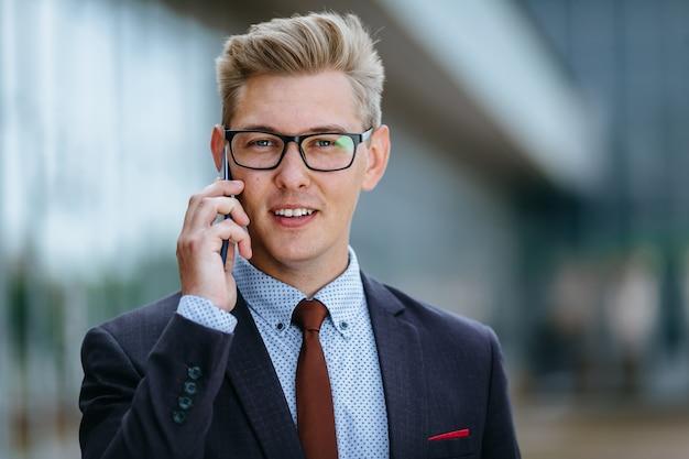 Mannelijke uitvoerende manager in trendy kleding met smartphone buitenshuis. modern technologie concept