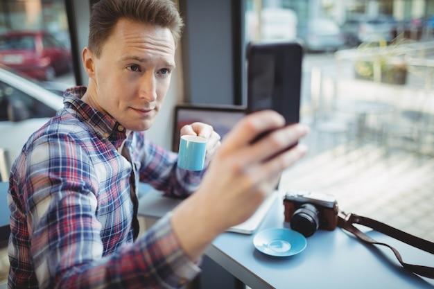 Mannelijke uitvoerende nemen selfie vanaf mobiele telefoon