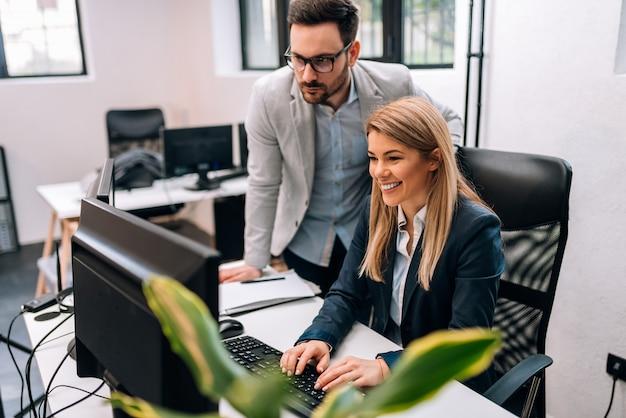 Mannelijke uitvoerende werkgever die het computerwerk van jonge vrouwelijke werknemer controleren.