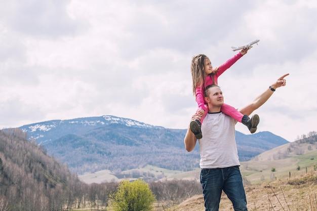Mannelijke vader en een klein babymeisje met wit stuk speelgoed vliegtuig in handen