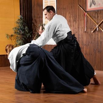 Mannelijke vechtsportinstructeur die in de oefenruimte traint met stagiair